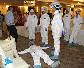 Workshop participants wearing hazmat suits and onlookers listen to a speaker in a conference room, actor lying on floor