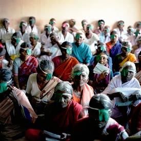 Many elderly Indian women in foreground and men in background seated on the floor, most wearing eye patches or bandages