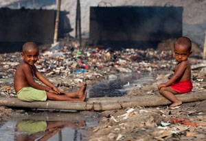 Two young, shirtless boys seated outdoors surrounded by garbage and rubbish, and stagnant water, background air is hazy
