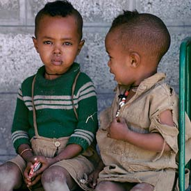 Two young boys seated, one looks at camera with swollen infected eye