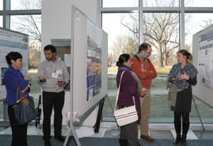 Hallway with scientific posters mounted on boards, researchers discuss their posters with conference attendees