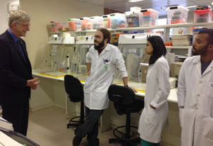 Dr Francis Collins stands in lab across from three young Brazilian researchers in white lab coats