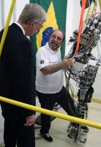 Dr Francis Collins observes as researchers demonstrates foot movement of a large metal robot, Brazilian flag hangs in background