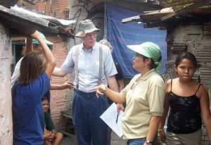 Dr. Richard Guerrant, center, speaks with team member and residents in a Brazilian shantytown next to run down buildings