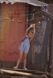 Young child hangs from empty clothesline in Brazilian slum