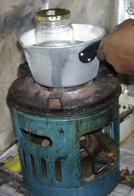 Pan of water, containing small jar with lid, being heated over small stove