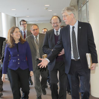 HHS secretary Burwell walks in Clinical Center hallway with NIH Dir Collins NCI Dir Varmus and NIH Deputy Dir Tabak