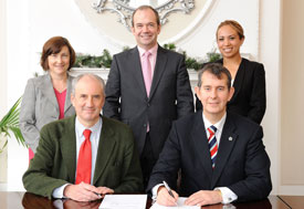 Health Minister Edwin Poots signing MOU with Dr Ted Trimble, Mary Jackson, Dr Michael McBride and Isabel Otero
