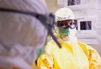 2 medical workers wearing personal protective equipment in the CDC mock Ebola treatment unit observe each other