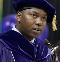 Dr Peter Cherutich speaks into a microphone wearing a purple doctoral tam and gown
