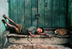 Young boy, barefoot and dirty, lies sleeping in doorway, appearing exhausted, dog curled up next to him on step