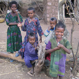 Five children look at and smile at the camera, playing in dirt courtyard, huts in background