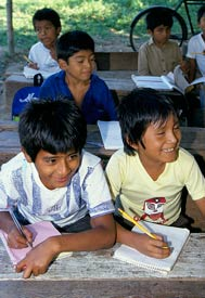 Two smiling boys write on paper pads on wooden desks in outdoor schoolhouse, more students in background do the same