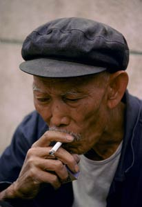 Older Chinese man smokes a cigarette