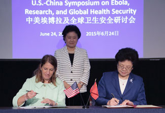 HHS Secretary Burwell and Chinese Minister Li Bin sign agreement, Chinese Vice Premier Liu Yandong watches, US and Chinese flags