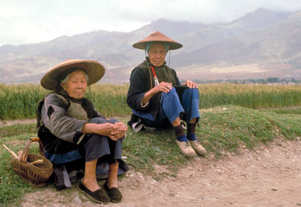 Two elderly women in china wearing Asian conical hats seated on the ground, farm fields and mountains in the background