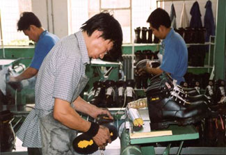 Chinese factory workers produce boots on a factory floor