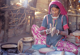 Woman sits cross-legged on ground rolling dough in hands, round flat bread cooking in pan on indoor cookstove