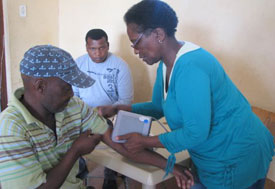 Man seated, arm on table, woman clinic worker places arm cuff around bicep to take blood pressure