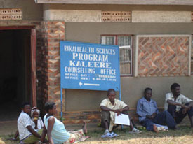 People seated on ground outside of building, sign on building reads Rakai health sciences program