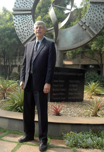 NIH Director Dr Francis S Collins stands in front of large genomics-inspired status in India