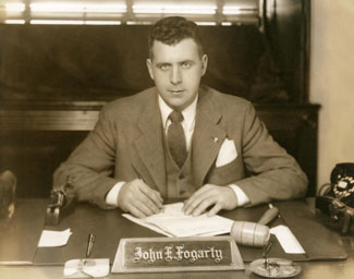 Black and white photograph of Congressman John E. Fogarty seated at a desk behind a nameplate with pen to paper