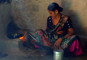 A woman seated on the floor next to a cookstove with a visible open flame adds wood to the fire