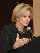 Woman speaks into a microphone at a podium, gestures with one hand