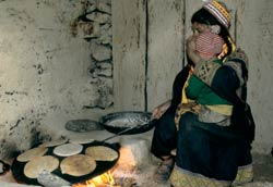 Woman squats, toddler on her lap, cooks large pan full of flat bread over indoor cookstove, flames visible beneath pan