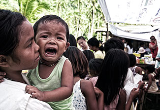 Crying child held while waiting in long line outdoors in the Philippines.
