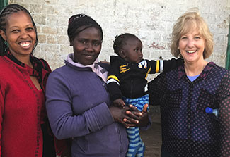 Dr. Debra Litzelman pictured with two women, one holding a baby, at a research site in Kenya