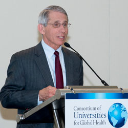 NIAID Director Tony Fauci speaks at a podium with sign reading Consortium of Universities for Global Health
