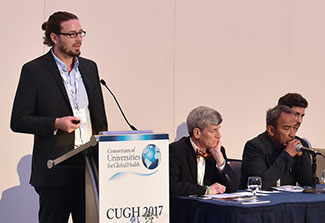 Male speaker in dress jacket speaks at a podium with sign that reads CUGH 2017, other panel members seated in background