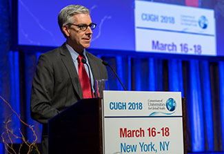 Dr. John Balbus speaks from a podium labeled CUGH 2018, slide projected in the background