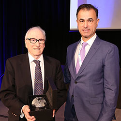 Fogarty's Dr. Ken Bridbord, holding award, stands next to CUGH's Dr. Keith Martin.