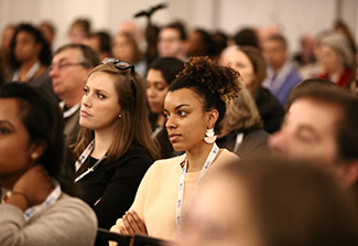 Attendees at the CUGH 2019 annual meeting listen attentively in a crowded conference room.