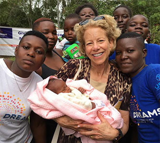 NICHD Director Dr. Diana Bianchi, center holding a baby, surrounded by young people in Kenya