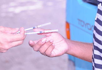 Close up of one hands of one person passing two syringe needles to another person