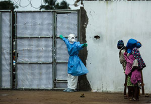 Healthcare worker outside Ebola clinic in full protective gear holds gate closed, warns away approaching people