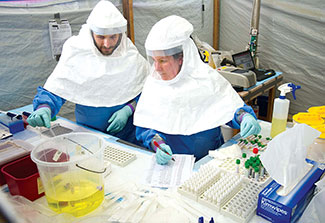 Two workers in personal protective gear test samples and record data in makeshift lab with tarp walls