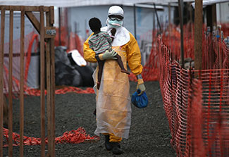 Health worker in personal protective equipment carries a child suspected of having Ebola in treatment center