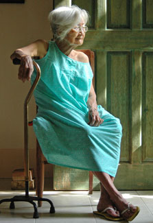 Frail looking elderly woman wearing a house dress seated in doorway leans on a cane