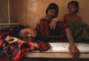 emaciated woman lying down in old hospital bed, two young children look on from behind