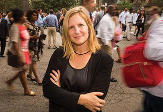 Dr. Emily Mendenhall poses on a street outdoors, many pedestrians walk on a busy street in the background.