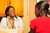 Woman medical worker in white coat with stethoscope around neck smiles and listens to woman patient in profile