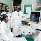 Medical workers in white coats observe large monitor