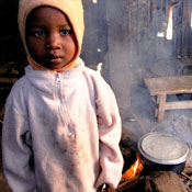 Young child in sweatshirt and hood looks into camera, fire burns with smoke in background