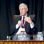 NIH Director Dr Francis Collins seated on a stage speaking into a hand-held microphone