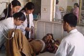 A weak looking man lies in metal frame hospital bed, medical workers examine him, 3 female standing, 1 male seated