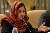 Iranian woman speaks into microphone at conference table